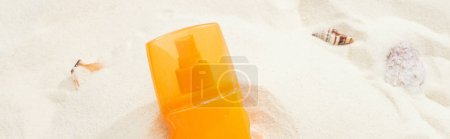 Photo for Orange bottle of sunscreen on sand with seashells, panoramic shot - Royalty Free Image