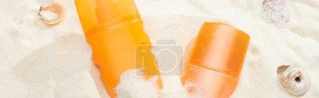Photo for Orange bottles of sunscreen on sand with seashells, panoramic shot - Royalty Free Image