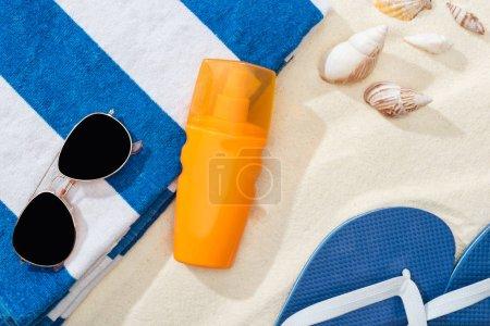 Photo pour Bouteille orange de crème solaire sur le sable près de la serviette rayée, des tongs bleues, des lunettes de soleil et des coquillages - image libre de droit