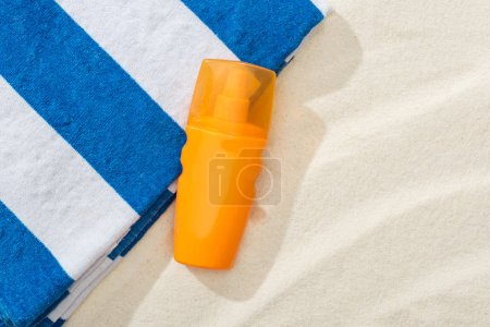 Photo for Orange bottle of sunscreen on sand with striped towel - Royalty Free Image