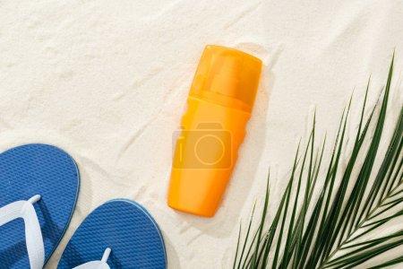 Photo pour Crème solaire orange près de la feuille verte de palmier sur le sable avec des tongs bleues - image libre de droit