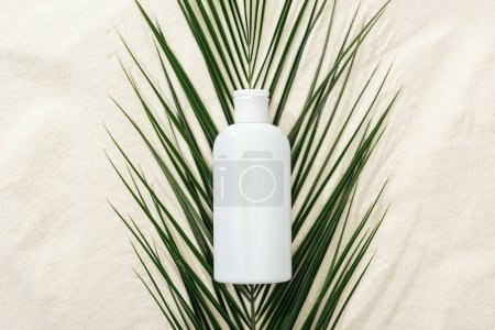 Photo for White sunscreen lotion on green palm leaf on sand - Royalty Free Image