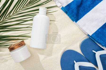 Photo for White sunscreen lotion and cream near green palm leaf on sand with blue flip flops and towel - Royalty Free Image