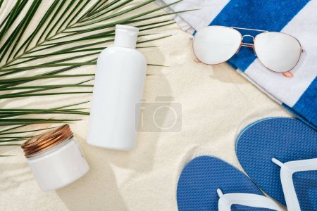 Photo for White sunscreen lotion and cream near green palm leaf on sand with blue flip flops, sunglasses and towel - Royalty Free Image