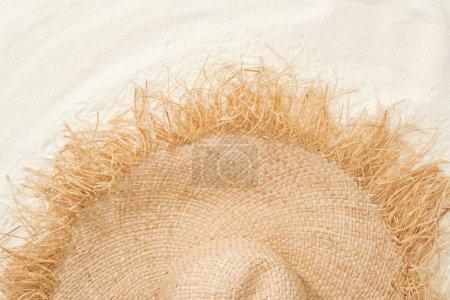 Photo pour Vue supérieure du chapeau élégant de paille sur le sable doré - image libre de droit