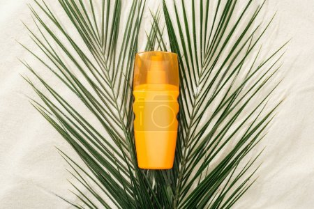 Photo for Orange sunscreen lotion on green palm leaves on sand - Royalty Free Image