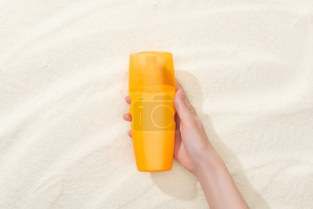 Photo for Cropped view of woman holding orange sunscreen above golden sand - Royalty Free Image