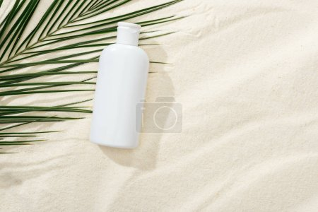 Photo for White sunscreen lotion near green palm leaf on sand - Royalty Free Image