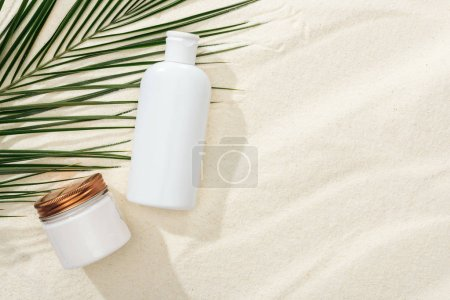 Photo for White sunscreen lotion and cream near green palm leaf on sand - Royalty Free Image