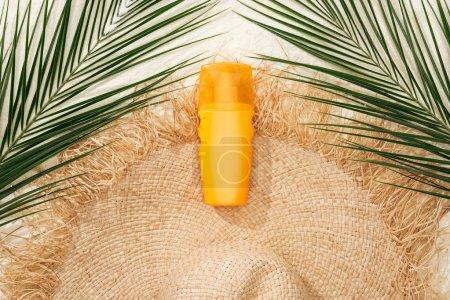 Photo pour Vue de dessus du chapeau de paille élégant sur sable doré avec feuilles de palmier vertes et crème solaire - image libre de droit