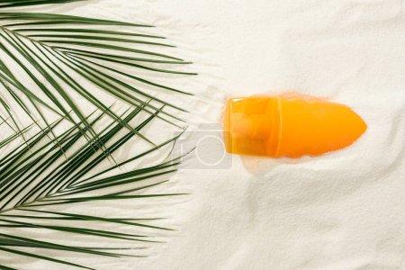 Photo pour Vue supérieure de la protection solaire et des feuilles vertes de paume sur le sable doré - image libre de droit