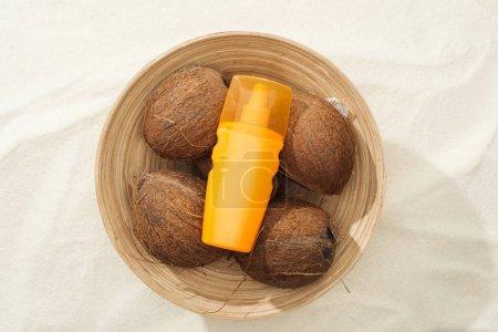 Photo pour Vue supérieure de la protection solaire dans le bol avec des noix de coco sur le sable doré - image libre de droit