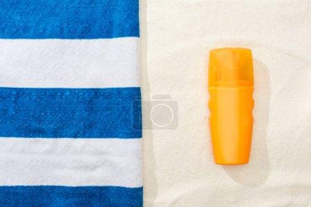 Photo pour Vue du haut de la protection solaire et serviette bleue et blanche rayée sur le sable doré - image libre de droit