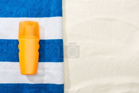 Photo for Top view of sunscreen and striped blue and white towel on sand - Royalty Free Image