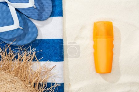 Photo for Top view of sunscreen, straw hat, flip flops and striped blue and white towel on golden sand - Royalty Free Image