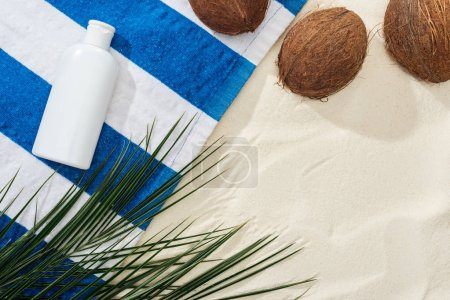 Photo for Top view of palm leaves, coconuts and striped towel with white sunscreen on sand - Royalty Free Image