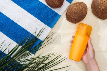 Photo pour Vue supérieure de la feuille de palmier, des noix de coco et de la main femelle avec la protection solaire sur le sable - image libre de droit