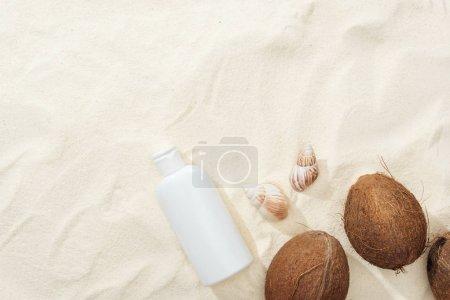 Photo pour Vue du haut des coquillages, des noix de coco et de la lotion solaire sur le sable - image libre de droit