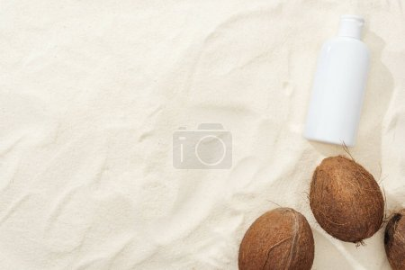 Photo for Top view of coconuts and white sunscreen lotion on sand - Royalty Free Image