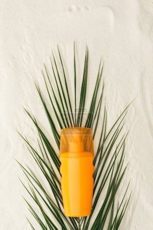 Photo for Top view of palm leaf and orange sunscreen on sand - Royalty Free Image