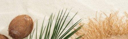Photo pour Vue du haut de la feuille de palmier, noix de coco et chapeau de paille sur le sable, projectile panoramique - image libre de droit