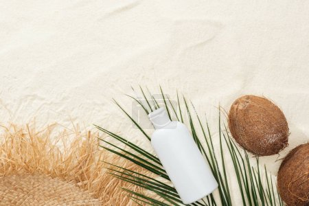 Photo for Top view of palm leaf, coconuts and sunscreen lotion with straw hat on sand - Royalty Free Image