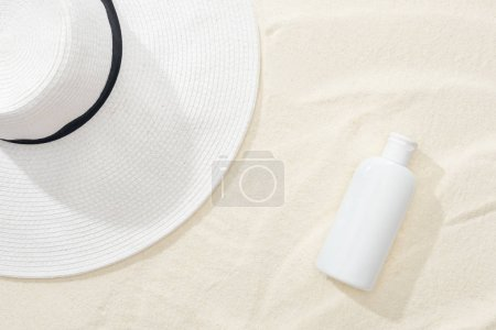 Photo for Top view of white sunscreen and straw hat on sand - Royalty Free Image