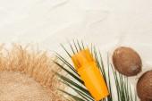 """Постер, картина, фотообои """"верхний вид пальмового листа, оранжевый солнцезащитный крем, кокосы и соломенная шляпа на песке"""""""