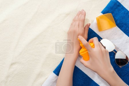 Photo for Cropped view of woman applying sunscreen on hands near striped towel and sunglasses on sand - Royalty Free Image