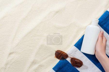 Photo pour Vue recadrée de femme retenant la protection solaire dans la main près de la serviette rayée et des lunettes de soleil sur le sable - image libre de droit