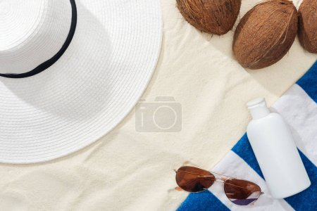 Photo for Top view of sunglasses, striped towel, coconuts and white straw hat near white lotion on sand - Royalty Free Image