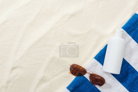 Photo for Top view of sunglasses, striped towel and white lotion on sand - Royalty Free Image