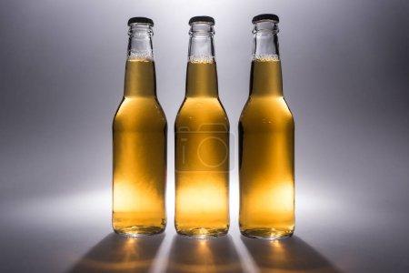 Foto de Tres botellas de vidrio con cerveza sobre fondo gris con luz de fondo - Imagen libre de derechos