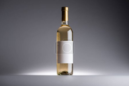 Photo for Bottle of white wine and blank label on dark background with back light - Royalty Free Image