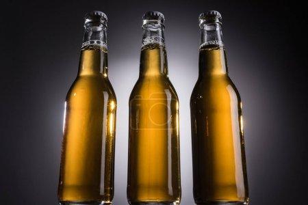 Photo pour Vue à angle bas de bouteilles en verre avec bière sur fond sombre avec contre-jour - image libre de droit