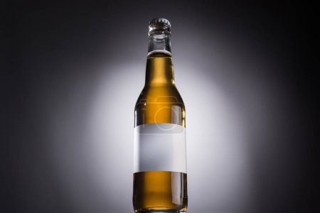 Photo for Low angle view of glass bottle with beer and white label on dark background with back light - Royalty Free Image