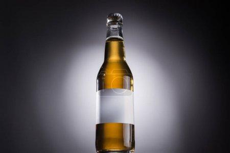 Photo pour Vue à angle bas de la bouteille en verre avec bière et étiquette blanche sur fond sombre avec contre-jour - image libre de droit