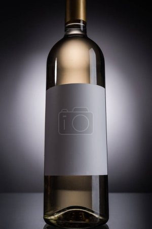 Photo for Low angle view of bottle with white wine and blank label on dark background with back light - Royalty Free Image