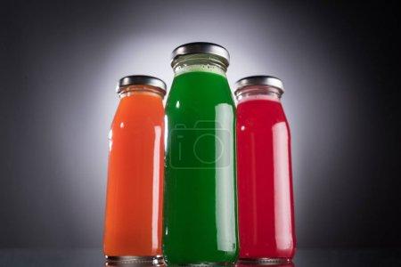 Photo pour Vue bas d'angle des bouteilles en verre avec le liquide coloré sur le fond foncé avec la lumière arrière - image libre de droit