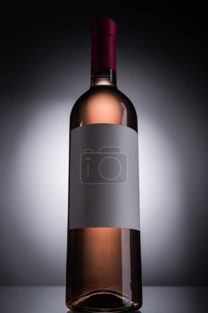 Photo for Low angle view of bottle with rose wine and blank label on dark background with back light - Royalty Free Image