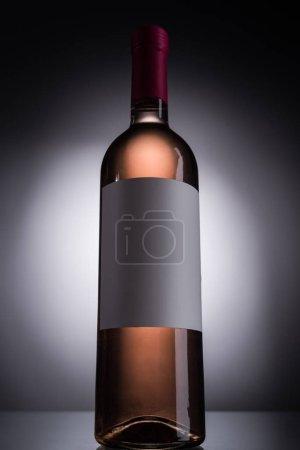 Photo pour Vue à angle bas de la bouteille avec vin rose et étiquette vierge sur fond sombre avec contre-jour - image libre de droit