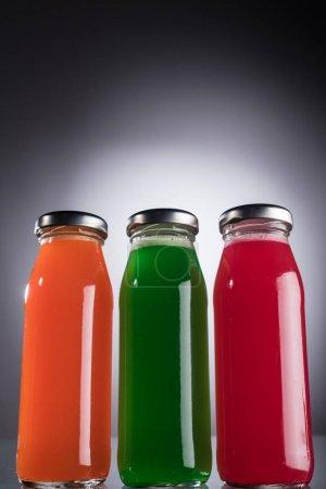Photo pour Vue d'angle bas des bouteilles en verre avec le liquide multicolore sur le fond foncé avec la lumière arrière - image libre de droit