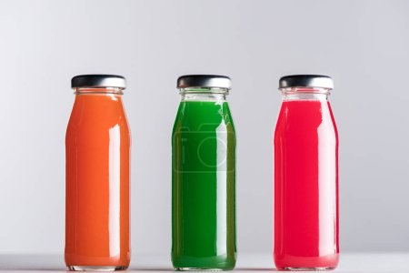 Photo pour Rangée de bouteilles en verre avec le jus multicolore isolé sur le gris - image libre de droit