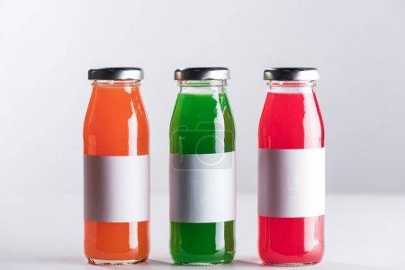 Photo pour Rangée de bouteilles en verre avec des étiquettes blanches et liquides multicolores isolées sur le gris - image libre de droit