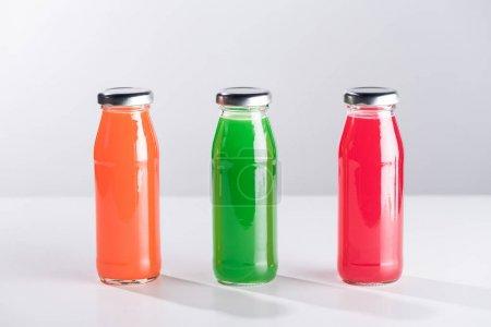 Photo pour Rangée de bouteilles en verre avec liquide multicolore isolé sur gris - image libre de droit