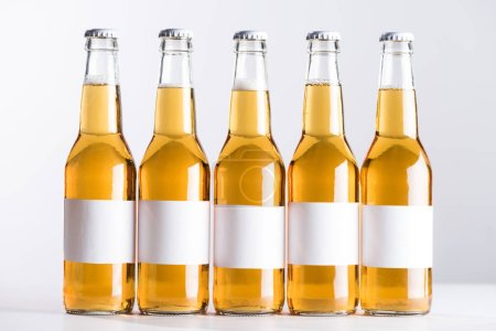 Photo pour Cinq bouteilles de bière avec des étiquettes blanches vierges isolées sur gris - image libre de droit
