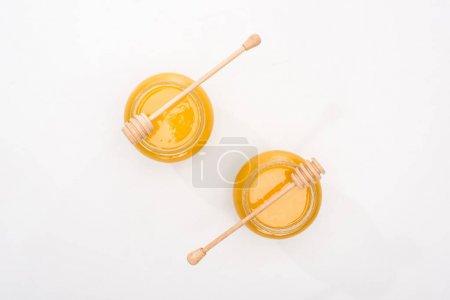 Foto de Vista superior de frascos con miel y dippers de miel de madera sobre fondo blanco - Imagen libre de derechos