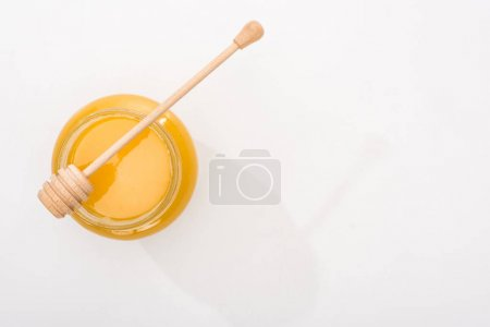 Photo for Top view of jar with honey and wooden honey dipper on white background with copy space - Royalty Free Image