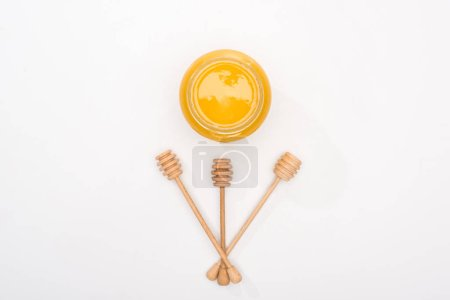Photo for Top view of jar with honey and wooden honey dippers on white background - Royalty Free Image