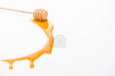Photo for Dripping honey and wooden honey dipper isolated on white with copy space - Royalty Free Image